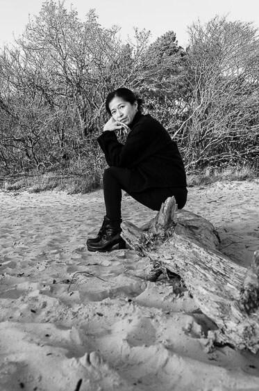 Afscheidsfotografe Hazel Ling die op een boomstam zit
