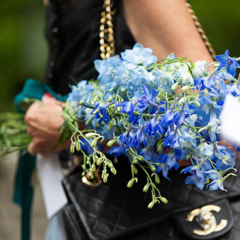 Afscheidsfotografie met een ingetogen en lichte benadering, legt vast hoe een familielid een paarse rouwboeket vasthoudt.