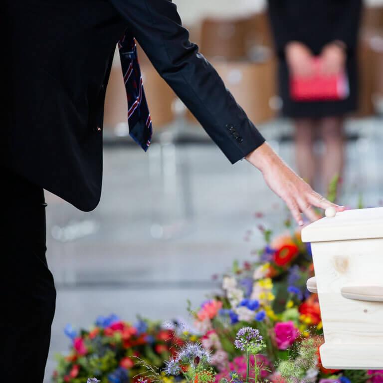Ingetogen afscheidsfotografie vangt het moment dat een vriend liefdevol zijn hand legt op de kist als laatste groet.