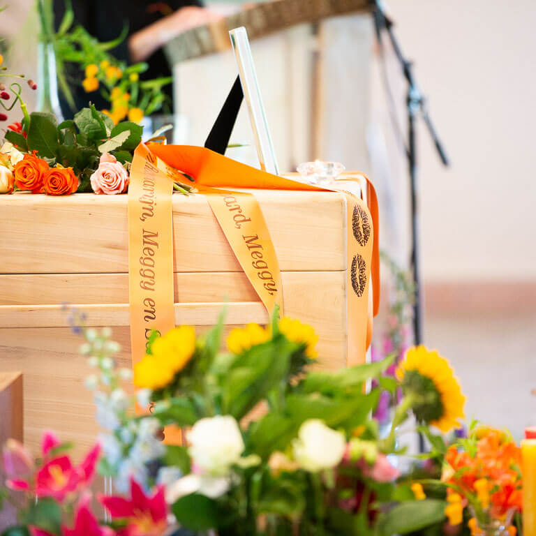 Op de afscheid staat een kist omringd met prachtig oranje rouwboeketten.