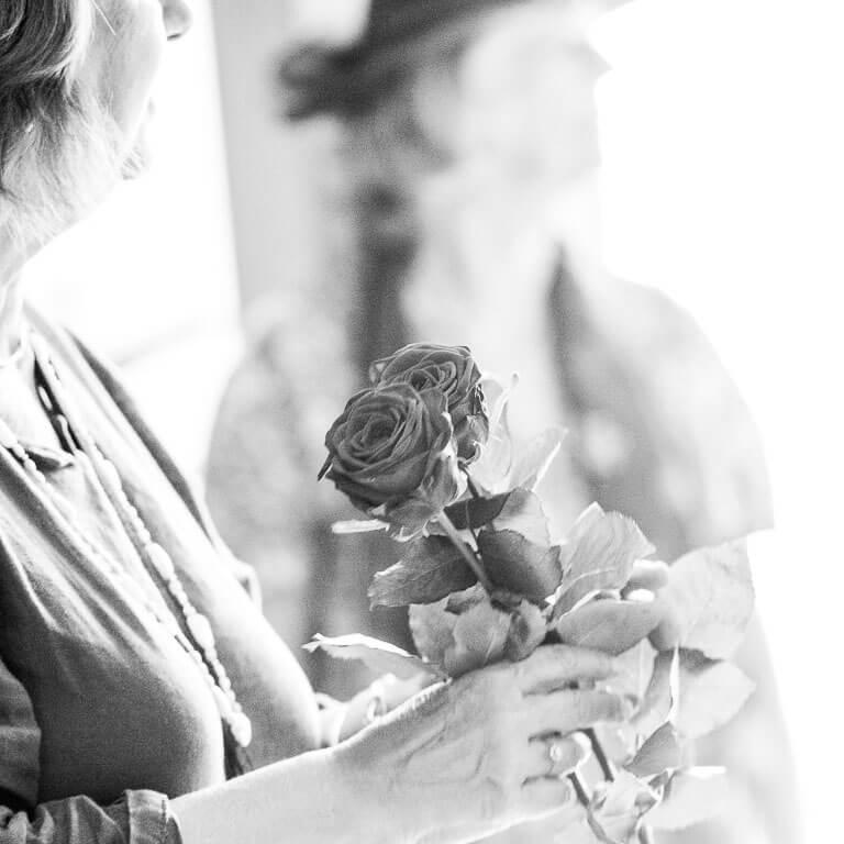 Rouwfotografie legt de sfeer vast. Een vrouw met rozen in haar hand komt de zaal binnen waar de uitvaartdienst plaatsvindt.
