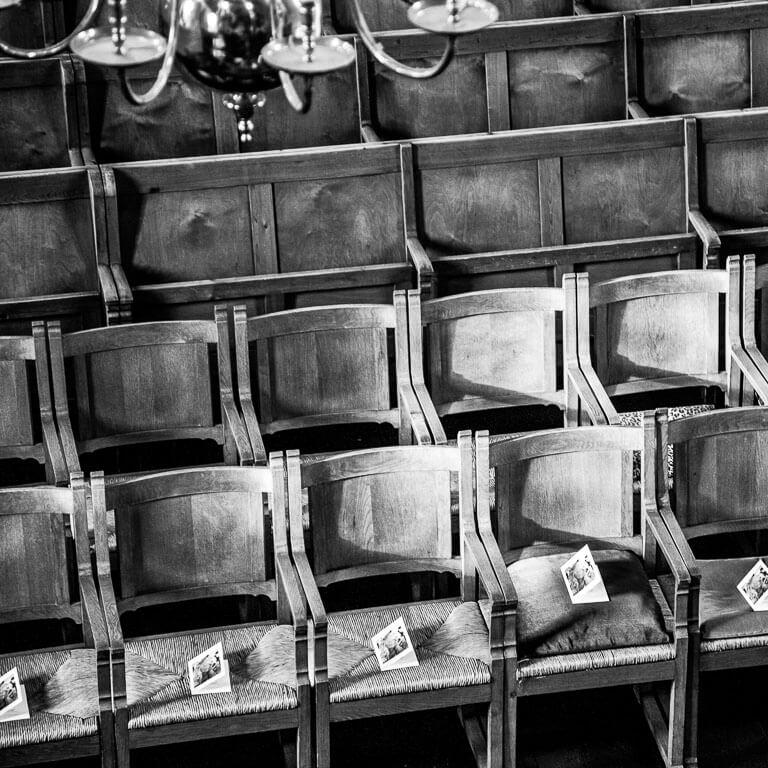 Sfeervolle afscheidsfotografie van programmaboekjes, die klaar zijn gelegd op stoelen voor de afscheidsdienst in een kerk.