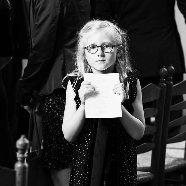 Afscheidsfotografie legt op sfeervolle wijze vast hoe een meisje bedroefd de rouwkaart in haar handen houdt.