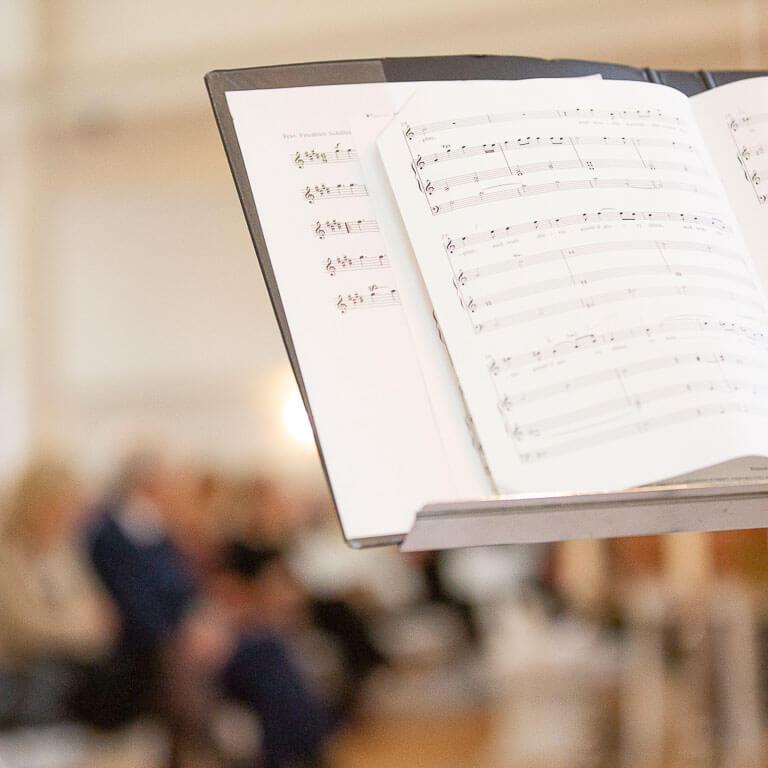 Discrete en respectvolle afscheidsfotografie legt de afscheidsdienst vast in de kerk waar je het muziekblad zichtbaar is.