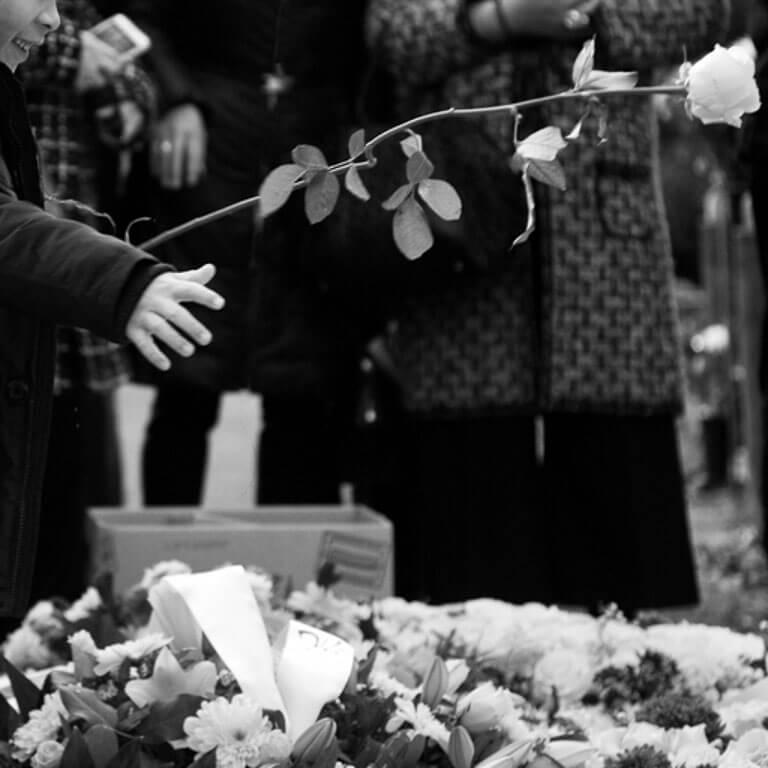 Afscheidsfotografie geeft troost door vast te leggen hoe liefdevol de kleinkind een roos werpt in de graf van zijn opa.