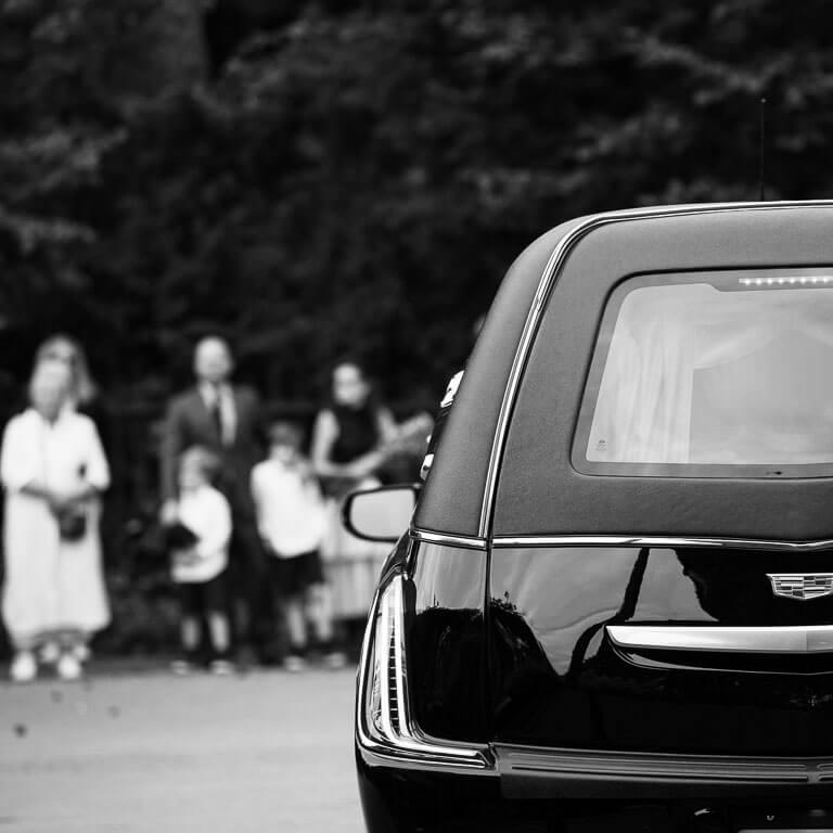 De rouwauto is aangekomen op de begraafplaats, terwijl familie en vrienden op de achtergrond staan te wachten.