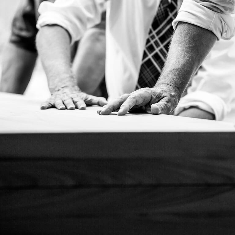 Op ingetogen wijze wordt vastgelegd hoe vrienden hun handen op de kist leggen van hun overleden vriend.