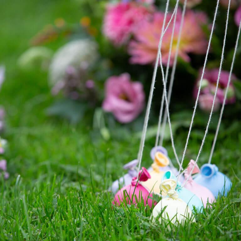 Kleurrijke ballonnen en rouwboeketten in het gras op een uitvaart.