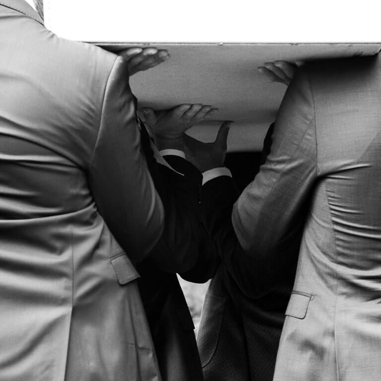 Ingetogen uitvaartfotografie laat de liefde zien van de familie en vrienden die de rouwkist op schouders dragen.