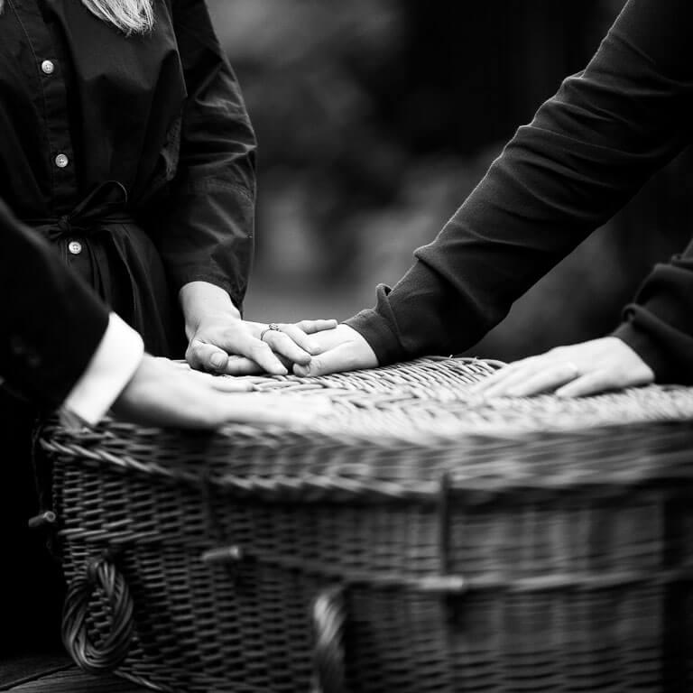 Ingetogen uitvaartfotografie legt de verbinding vast. Vrienden en familie leggen samen hun handen op het grafmandje.