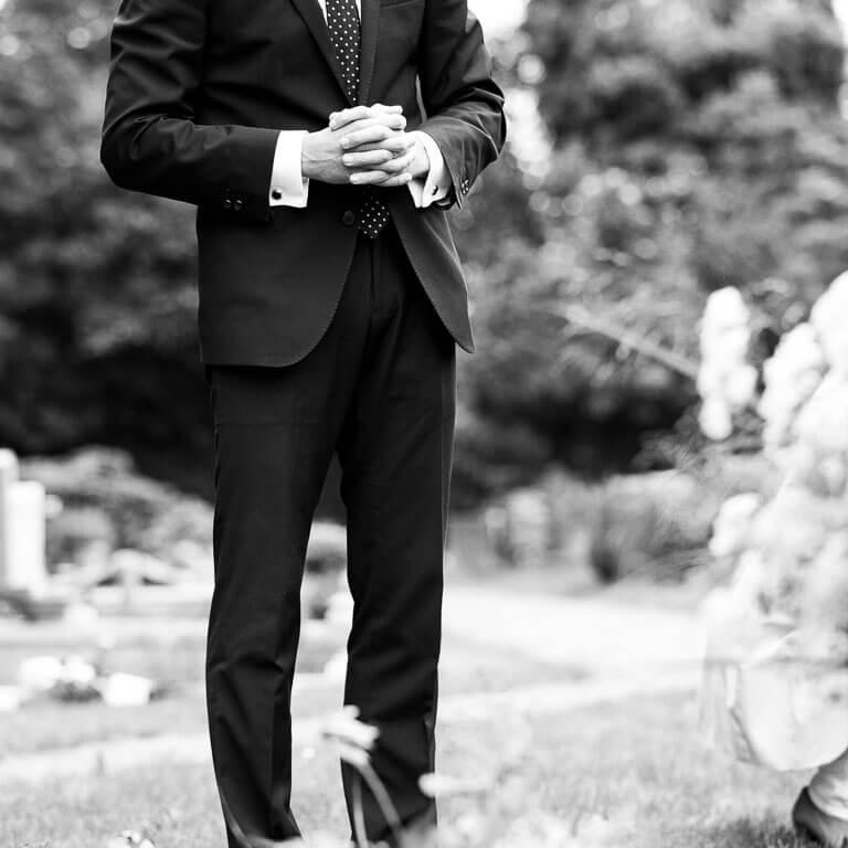 Uitvaartfotografie laat op ingetogen wijze zien hoe een vader een gebed doet bij het graf van zijn overleden dochter.