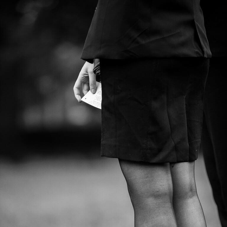 Ingetogen rouwfotografie van een vrouw een kaartje in haar hand die in de rij staat bij de condoleance.